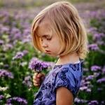 Kind houdt bloemen vast. Foto door Anna Niezabitowska op Unsplash